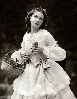 Actress, Dorothy Gish, wearing a long-sleeved white dress with tiered skirt, standing in a bed of flowers, holding a small basket full of flowers, from the film The Streets of New York. (Photo byEdward Steichen/Condé Nast via Getty Images)